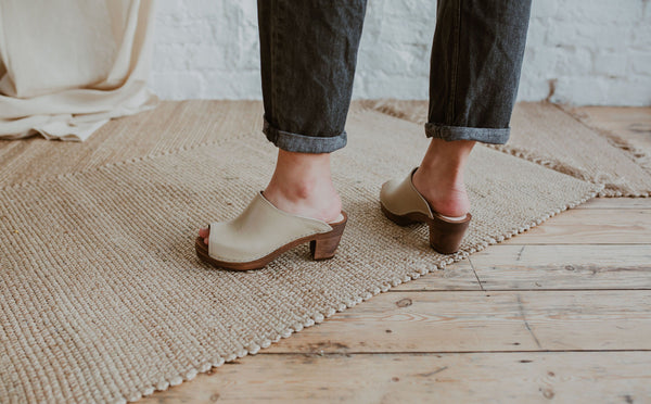 close up of woman's feet in Stone beige coloured classic style mid heel swedish clog with a peep toe