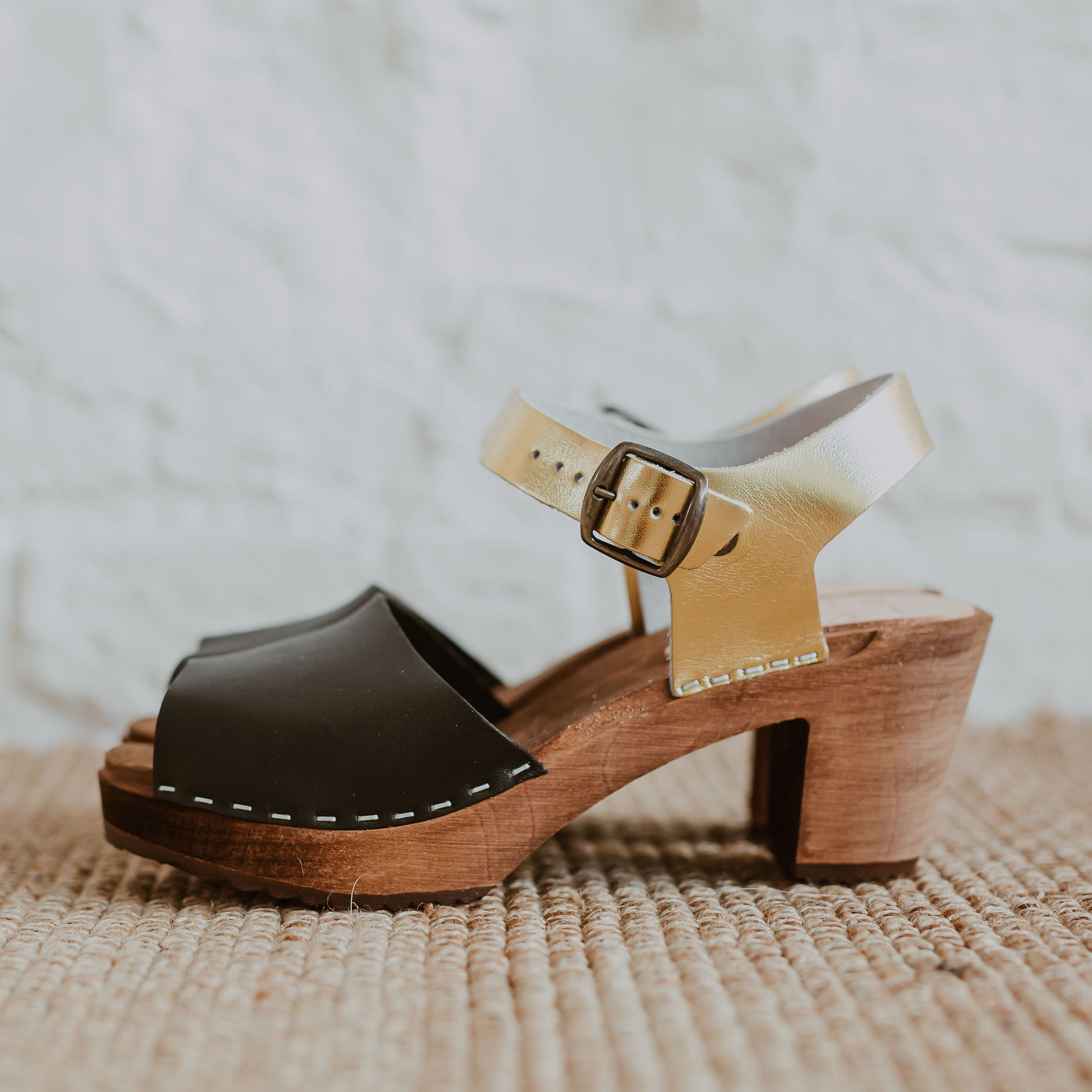 two tone black onyx and gold peep toe swedish clog with a mid heel