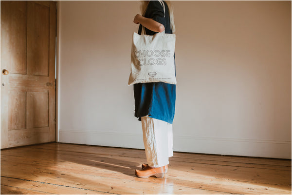 choose clogs charity tote bag held over the shoulder by a woman wearing cumin low jord clogs and a denim shirt dress