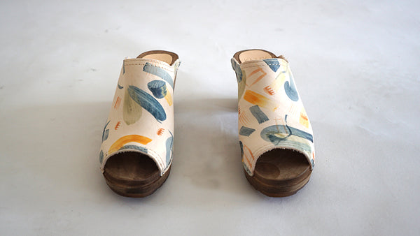 mid heel swedish clog with an open back, a peep toe and hand-painted leather uppers with an abstract shape pattern