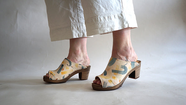 close up of woman's feet in mid heel swedish clog with an open back, a peep toe and hand-painted leather uppers with an abstract shape pattern