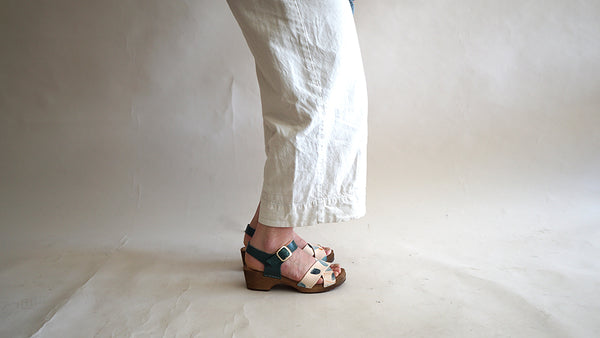 close up of woman's feet in low heel clog sandal with hand-painted straps a contrasting blue/green leather ankle strap