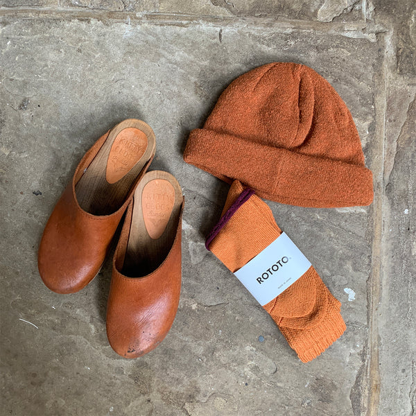 burnt orange knitted beanie hat, clogs and socks