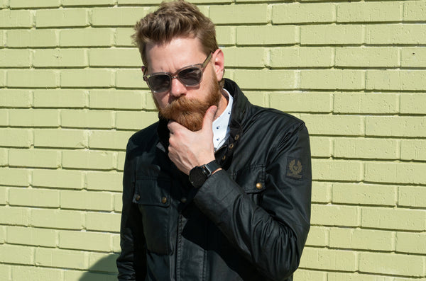 Eric Bandholz standing in front of a green wall and stroking his beard.