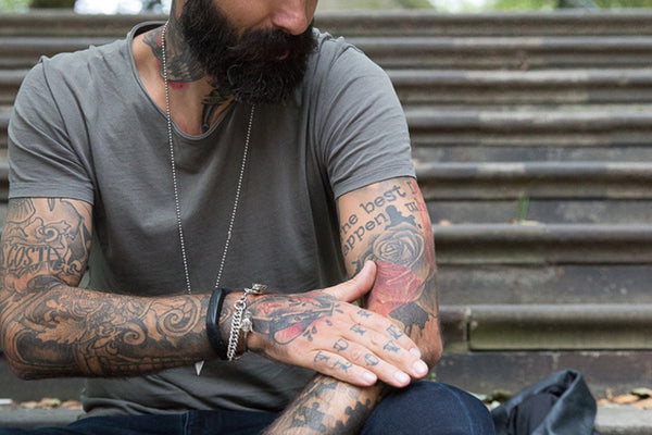 Close up of Carlos Costa's arms, displaying his badass tattoos.
