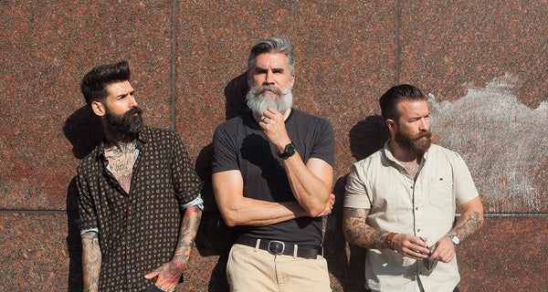 Carlos Costa, Greg Berzinsky, and Jeffrey Buoncristiano have thick beards and are standing together in front of a wall.