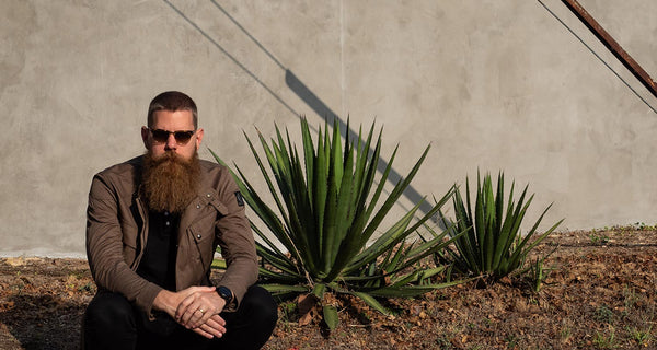 Eric Bandholz has a buzz cut and long beard, and is squatting in front of a cement wall.