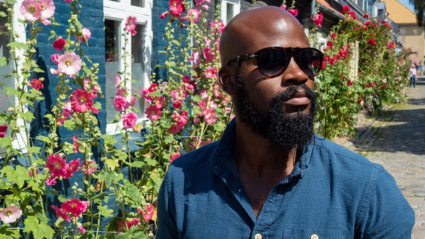 Manscaped Black man with a bald head and thick beard is wearing dark sunglasses and standing in front of flowers.