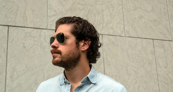 Man with curly coarse hair wearing Ray-Ban Aviators