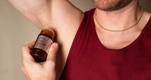 White man in a red tank top applying Beardbrand Deodorant to his armpit.