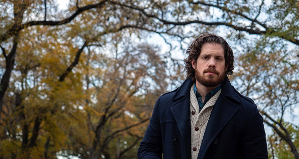 Man with a beard wearing a navy peacoat and standing in front of autumn trees.