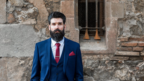 Carlos Costa has an amazing beard style and is wearing a blue 3-piece suit and red tie.