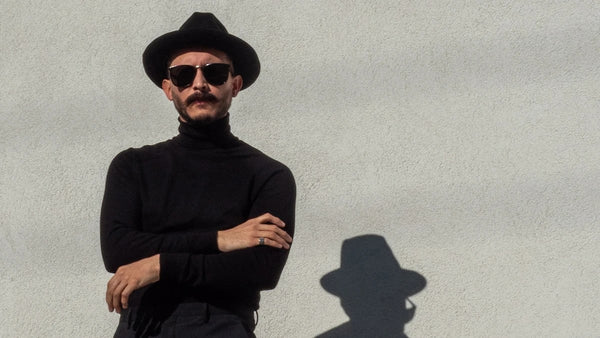 Stylish man with a goatee wearing a black fedora and turtleneck