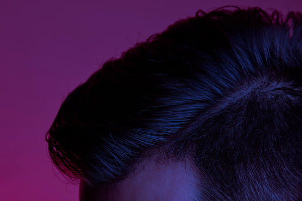 Close up of a white man's luscious, brown side-parted hair.