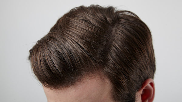 Close up of a white male's stylish brown, side-parted hair after using shampoo and conditioner.