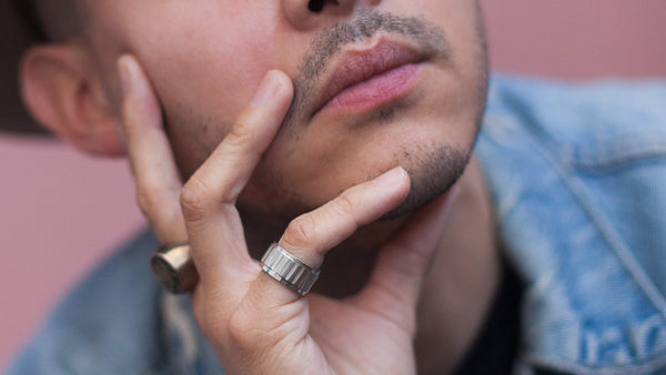 Close up of a man touching his face. He has clear, healthy skin and facial hair stubble.