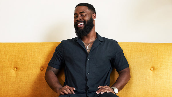 Stylish Black man with a thick beard, smiling and sitting on a yellow couch.