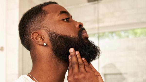 Profile of a handsome black man feeling his long beard.