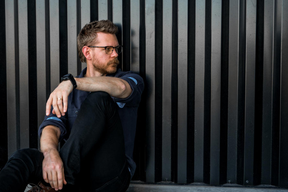 Beardbrand Founder, Eric Bandholz, sitting against a dark wall and looking to his left.