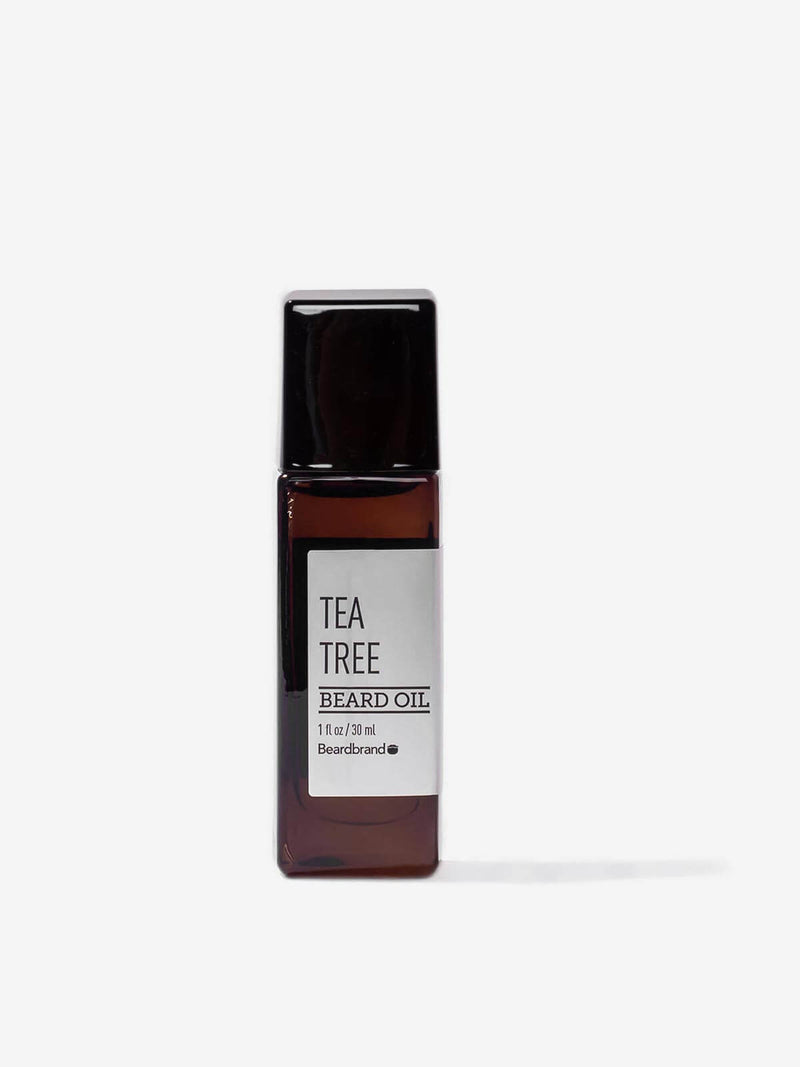 A bottle of Beardbrand Tea Tree Beard Oil on a striking gray backdrop.