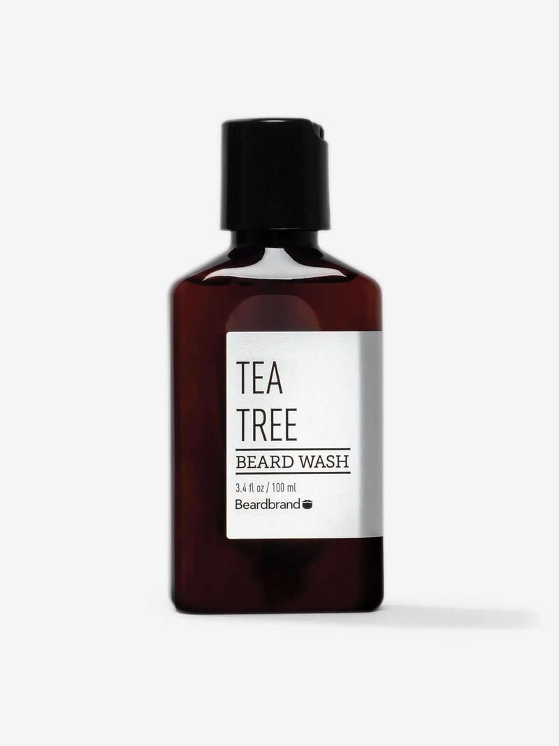 A bottle of Beardbrand Tea Tree Beard Wash on a striking gray backdrop.