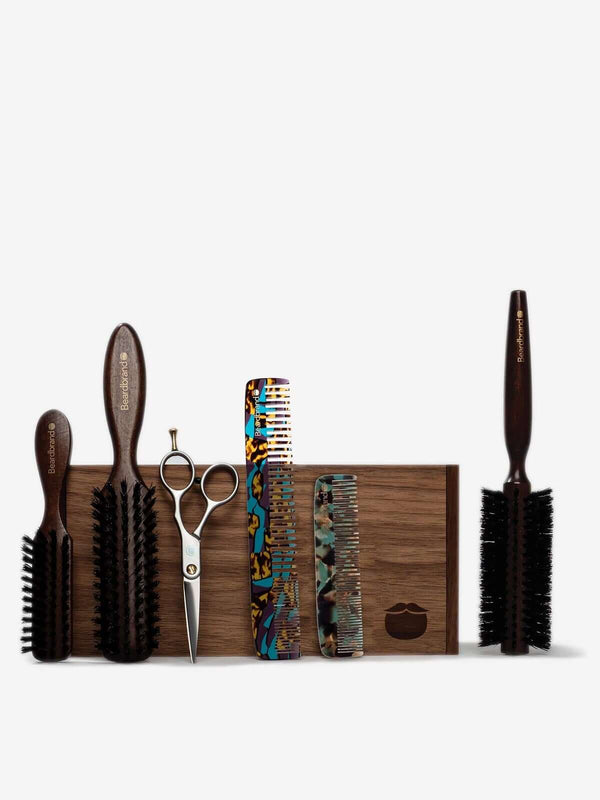 Beardbrand grooming tools lined up and leaning against a wooden Beardbrand Beardsman's Box.