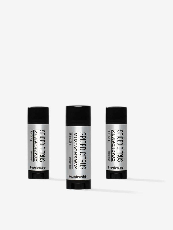 Three pocket-sized tubes of Beardbrand Spiced Citrus Mustache Wax on a striking grey backdrop.