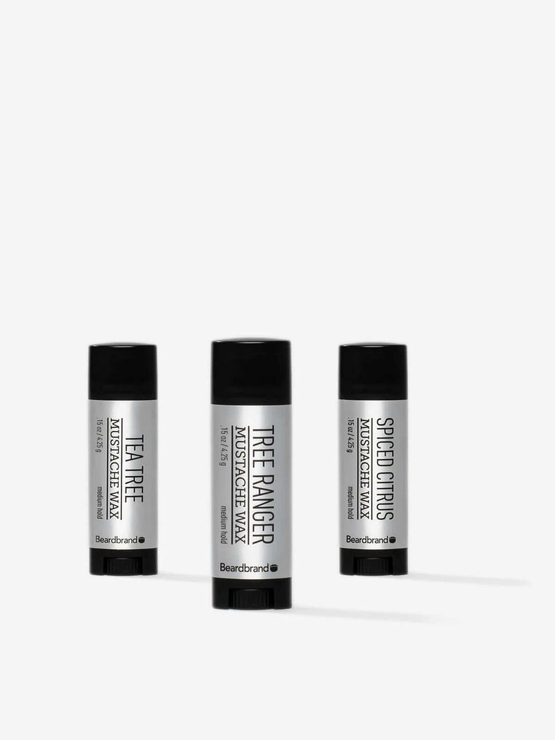 Three pocket-sized tubes of Beardbrand Silver Line Mustache Wax on a striking grey backdrop.