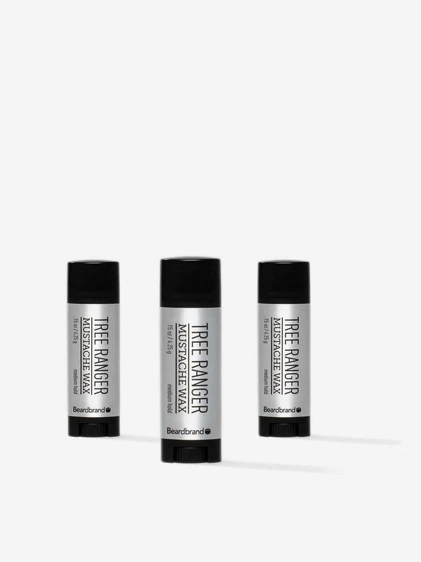 Three pocket-sized tubes of Beardbrand Tree Ranger Mustache Wax on a striking grey backdrop.