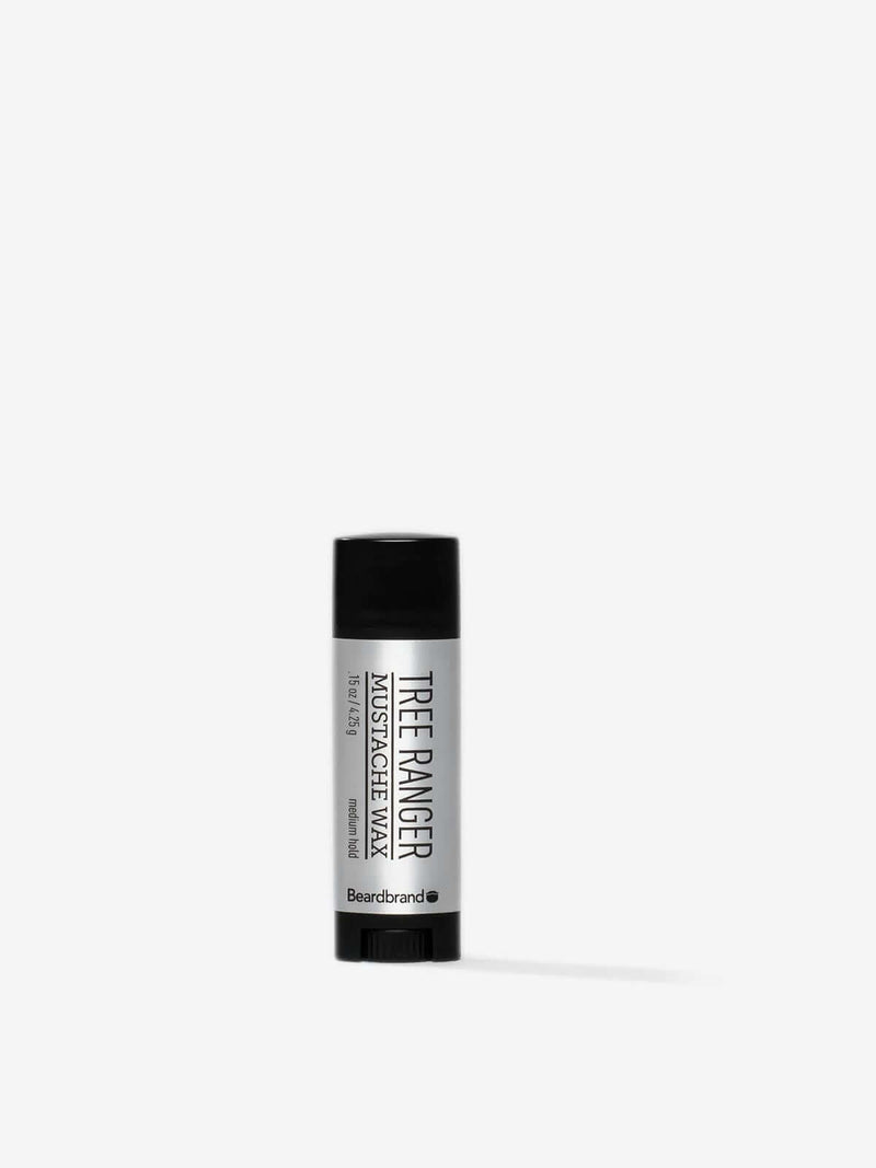 A tube of Beardbrand Tree Ranger Mustache Wax on a striking gray backdrop.