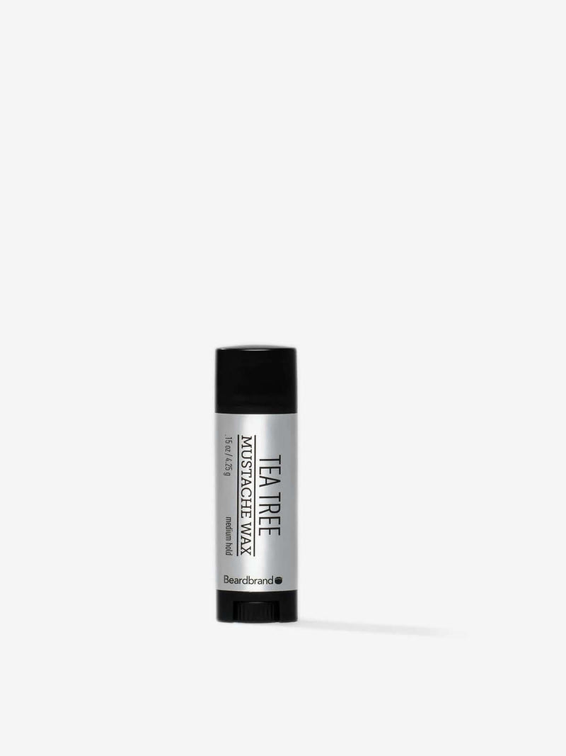 A tube of Beardbrand Tea Tree Mustache Wax on a striking gray backdrop.