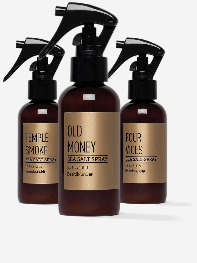Three bottles of Beardbrand Gold Line Sea Salt Spray—Four Vices, Old Money, and Temple Smoke.