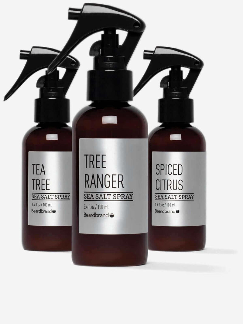 Three bottles of Beardbrand Silver Line Sea Salt Spray—Spiced Citrus, Tree Ranger, and Tea Tree.