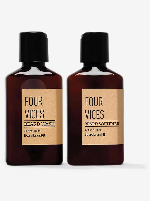 A bottle of Beardbrand Four Vices Beard Wash next to a bottle of Four Vices Beard Softener on a striking gray backdrop.