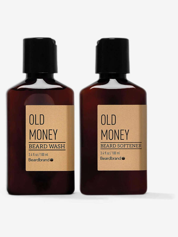 A bottle of Beardbrand Old Money Beard Wash next to a bottle of Old Money Beard Softener on a striking gray backdrop.