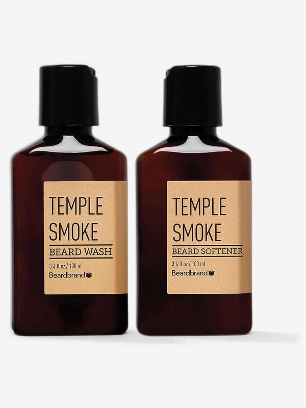 A bottle of Beardbrand Temple Smoke Beard Wash next to a bottle of Temple Smoke Beard Softener on a striking gray backdrop.