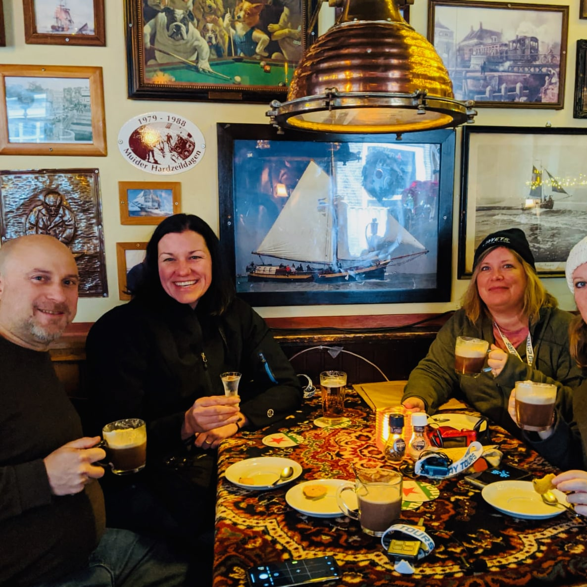 three women and one man enjoying hot beverages in an authentic old brown cafe in holland