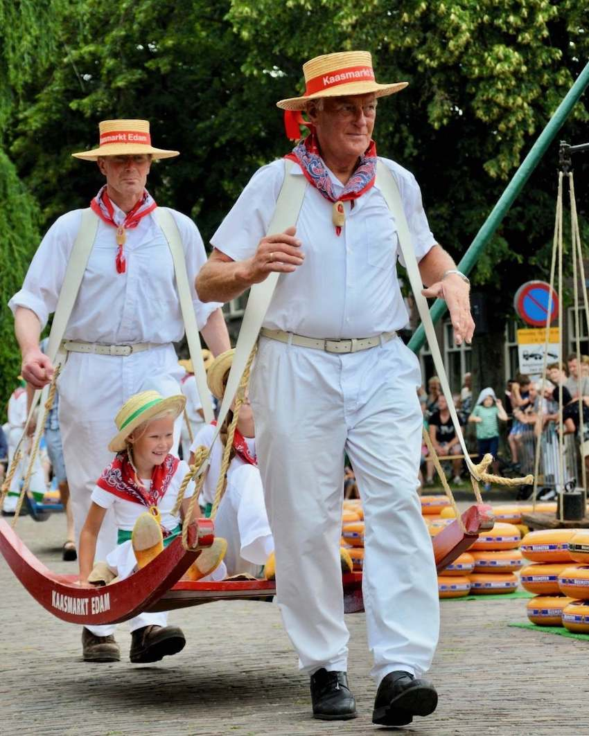 image of two men carrying a girl at the Edam cheese market