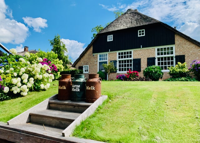 a traditional dutch farmhouse in giethoorn with all sorts of flowers in the garden