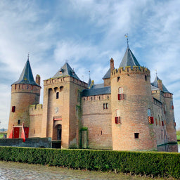 The small castle of Amsterdam Muiderslot in Holland is surrounded by a moat with a clear blue sky