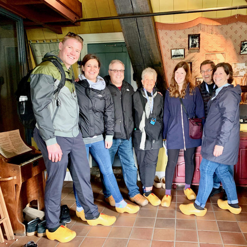 a family on a private tour with tulip day tours are wearing wooden clogs in windmill Blokweer that is part of world heritage site Kinderdijk
