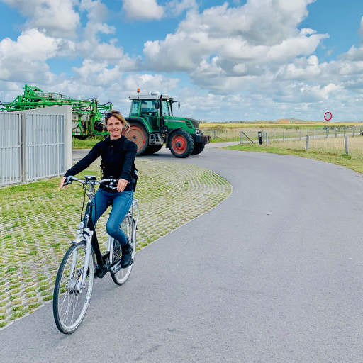 a beautiful image of tour guide on a bicycle on the island of texel waddensea with tulip day tours