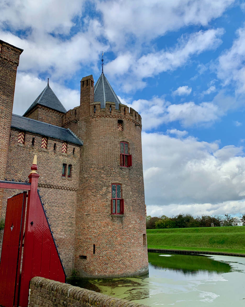 Image of one of the towers of Muiderslot Castle with a cloudy sky as background