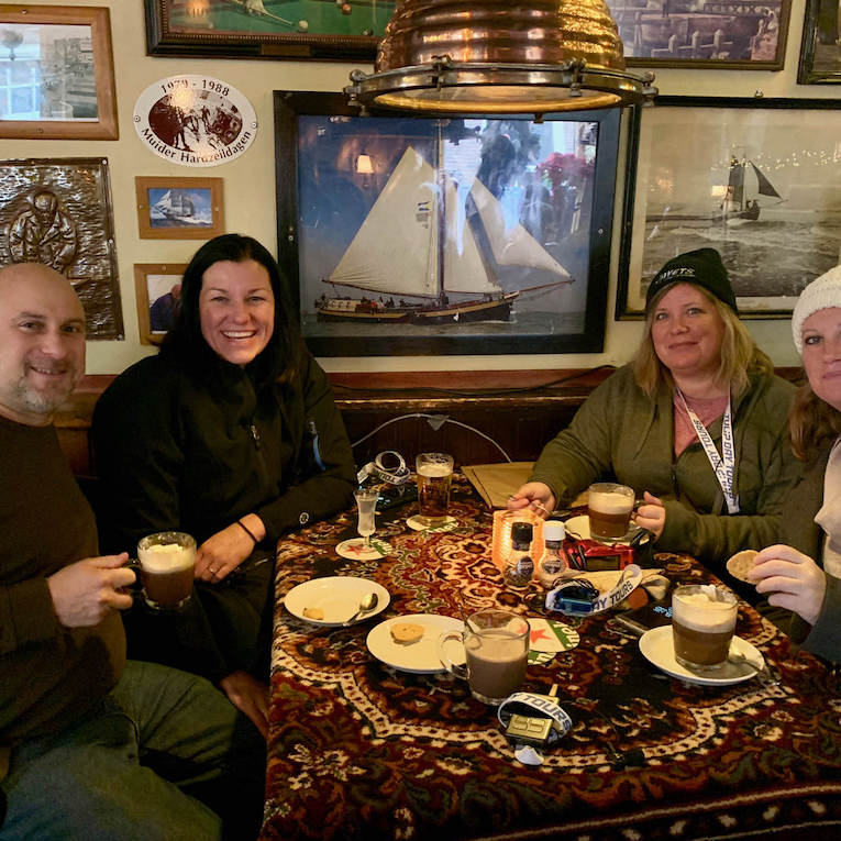 Four travelers experiencing Dutch culture in a traditional brown cafe with                                                                                                                                     Tulip Day Tours