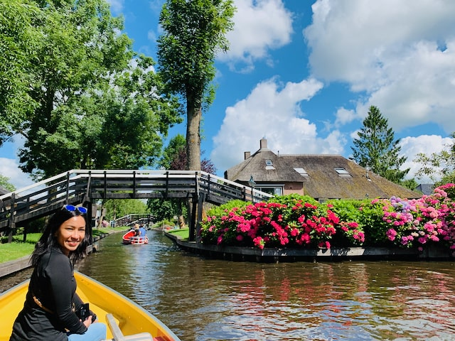 a woman on a private tour to Giethoorn sits in the front of an electrical whisper boat