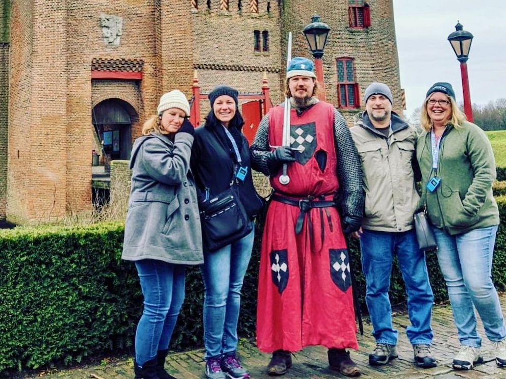 four people enjoying a private tour to  keukenhof and amsterdam castle with tulip day tours pose for the picture with a knight in front of the drawbridge of Amsterdam Muiderslot Castle