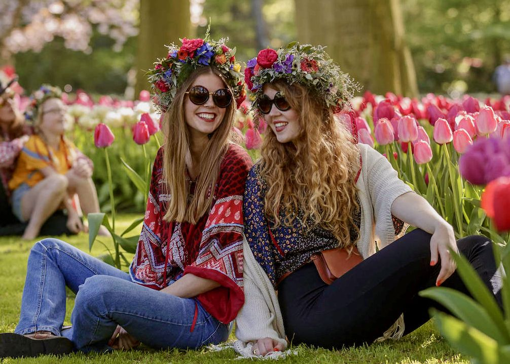 two girls on a public tour to Keukenhof Tulip Gardens sitting in the flowers with tulip day tours