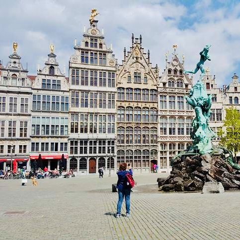 a woman in a private tour with tulip day tours takes a picture of Brabo on the market square of Antwerp