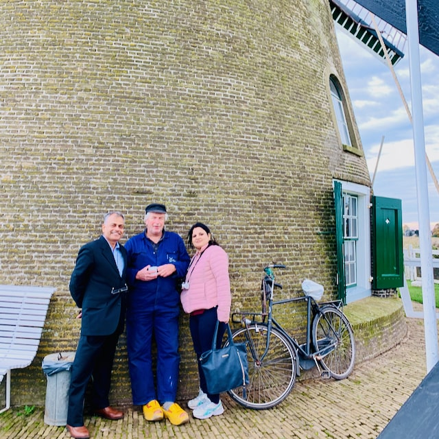 travelers from india enjoying a private tour talk with the miller in front of his windmill in kinderdijk