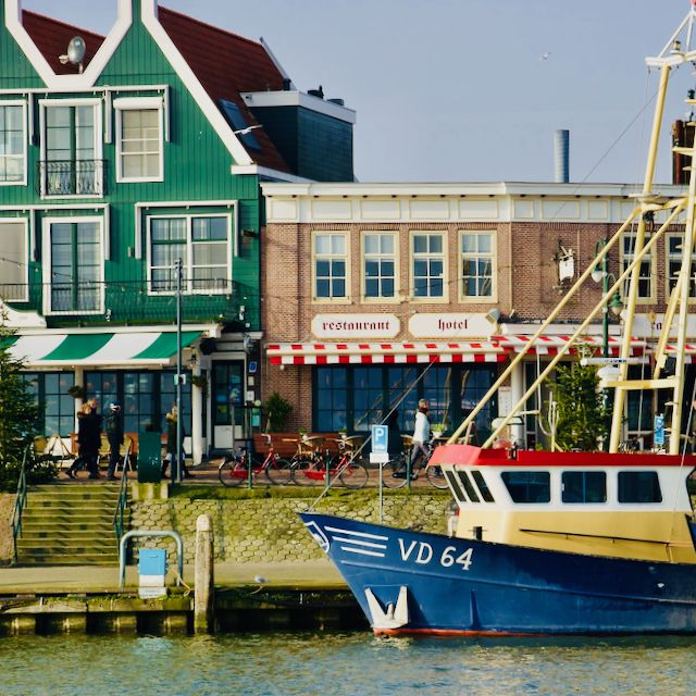 a Dutch blue ship docked along the dyke in Volendam